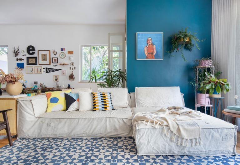 sala com parede azul e almofadas coloridas