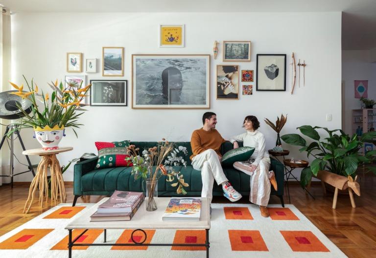Sala com tapete colorido, sofá verde e muitas plantas
