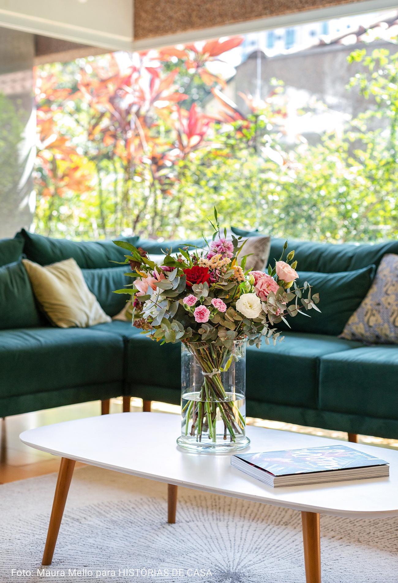 mesa de centro branca com flores e livro