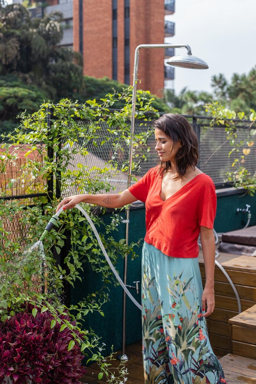 mulher regando plantas em quintal suspenso