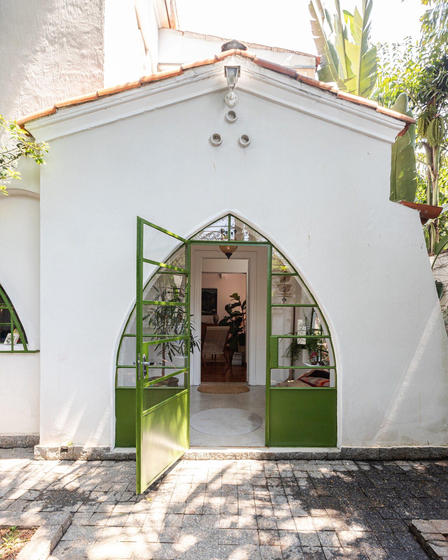 Casa antiga com portas de serralheria verde