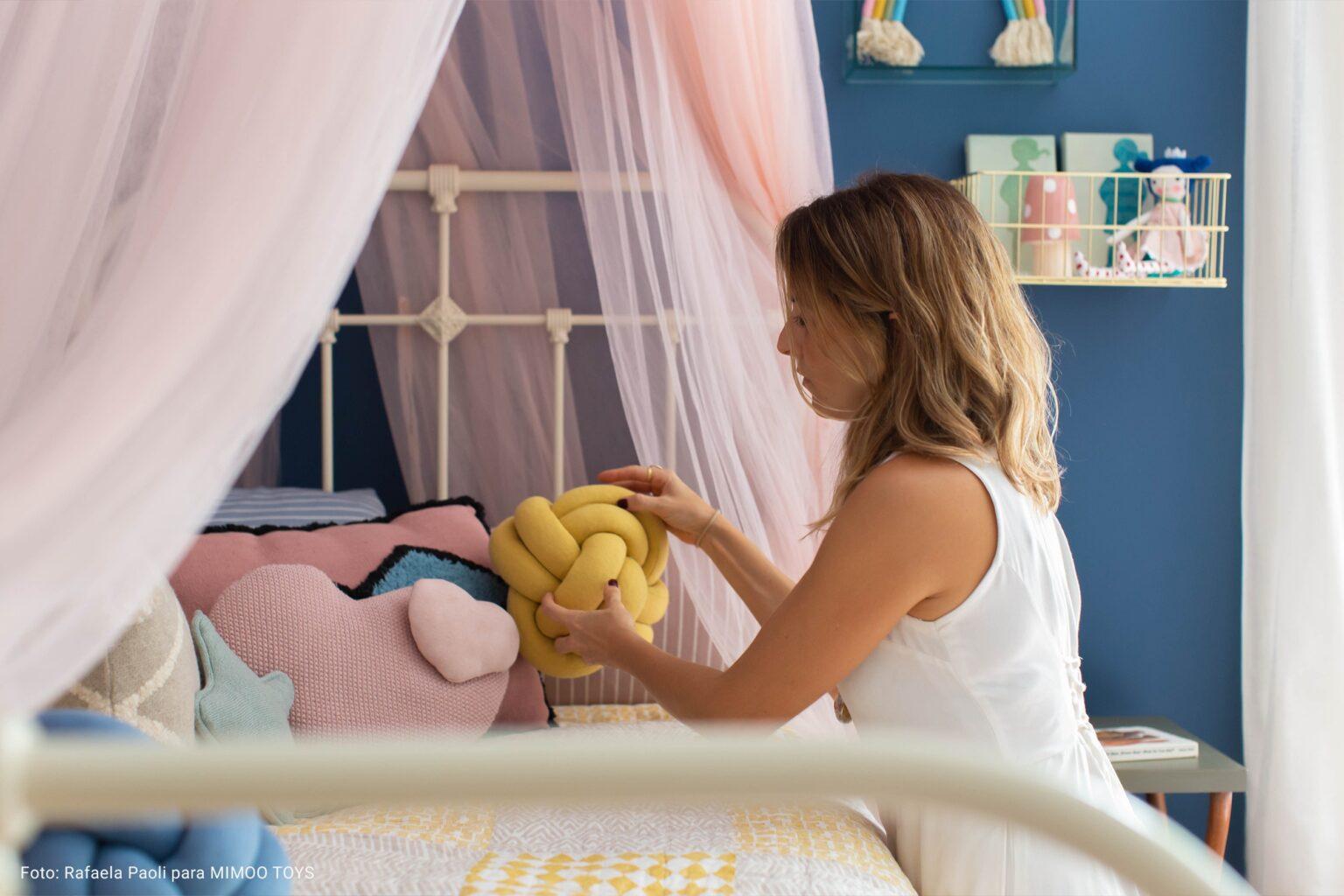 mulher colocando almofada em cama