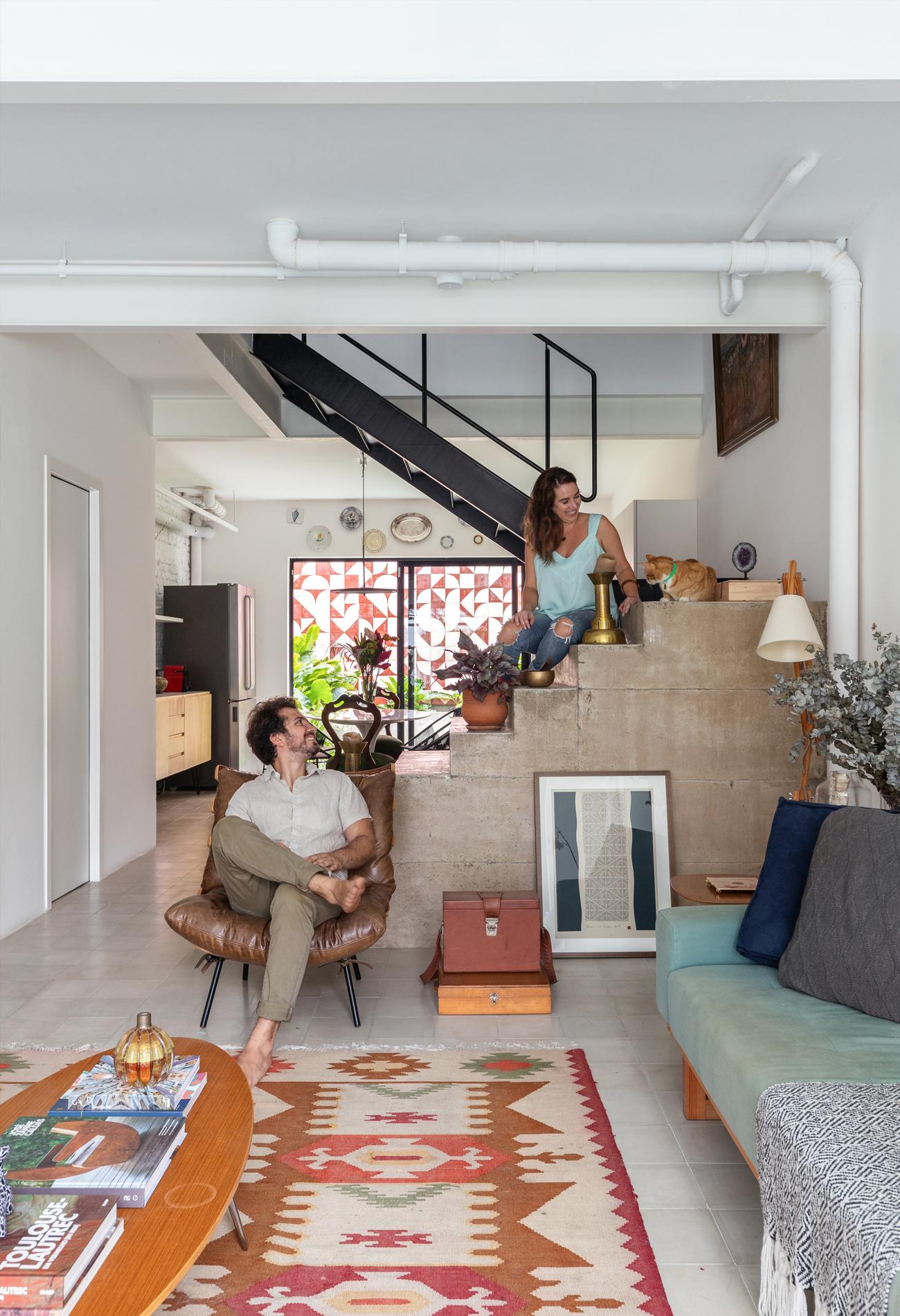 Casa com escada de concreto e tapete colorido