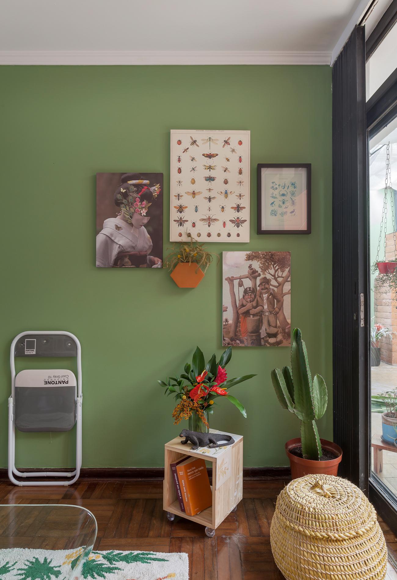 Sala com parede pintada de verde e quadros