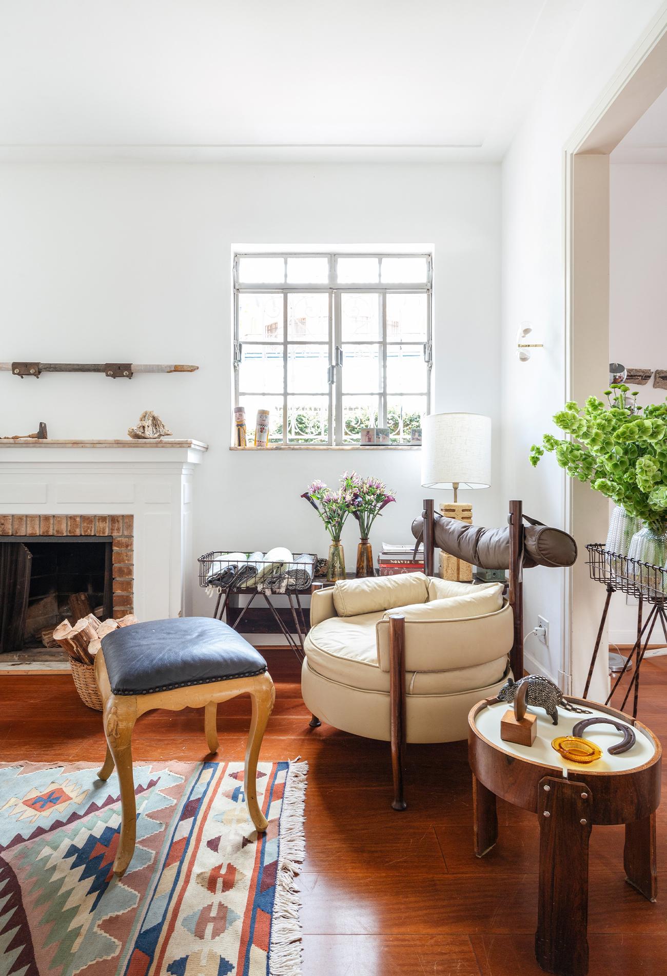 decoração sala com lareira, poltrona sergio rodrigues e mesa madeira