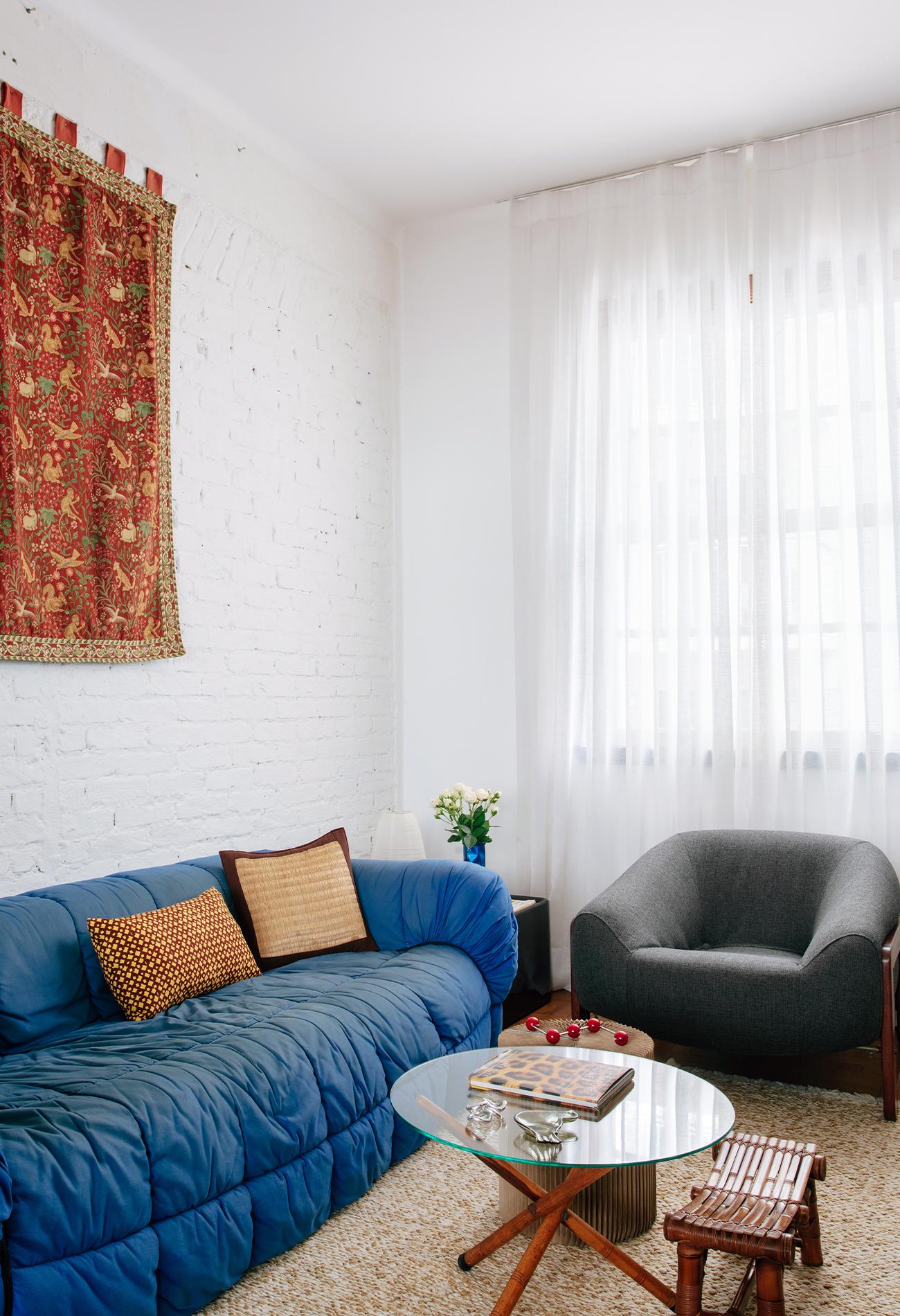 Sala com parede de tijolinho branco e sofá azul
