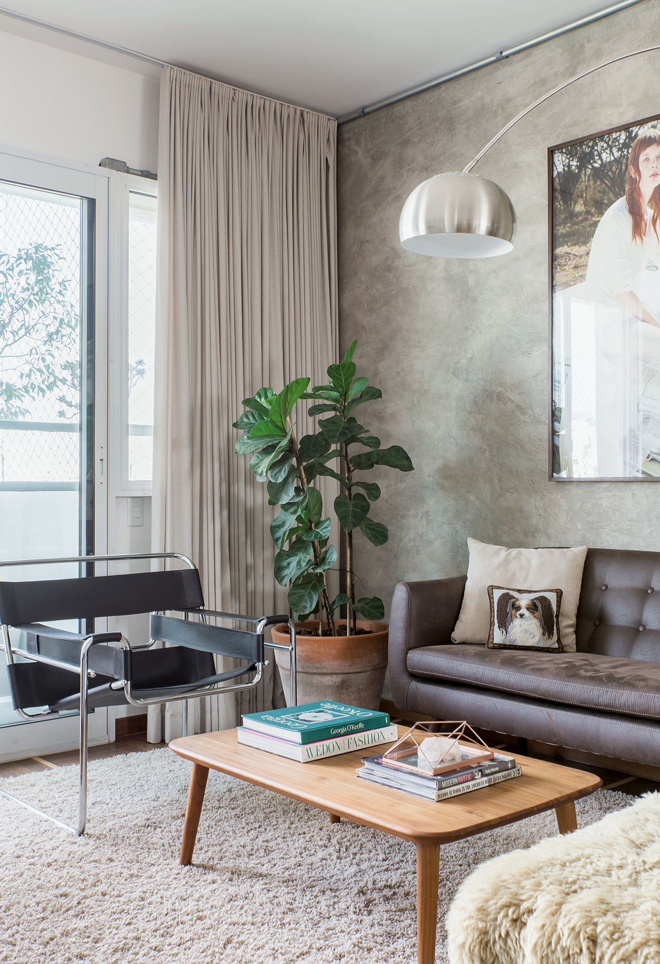 Sala com parede de cimento queimado e sofá de couro, estilo industrial