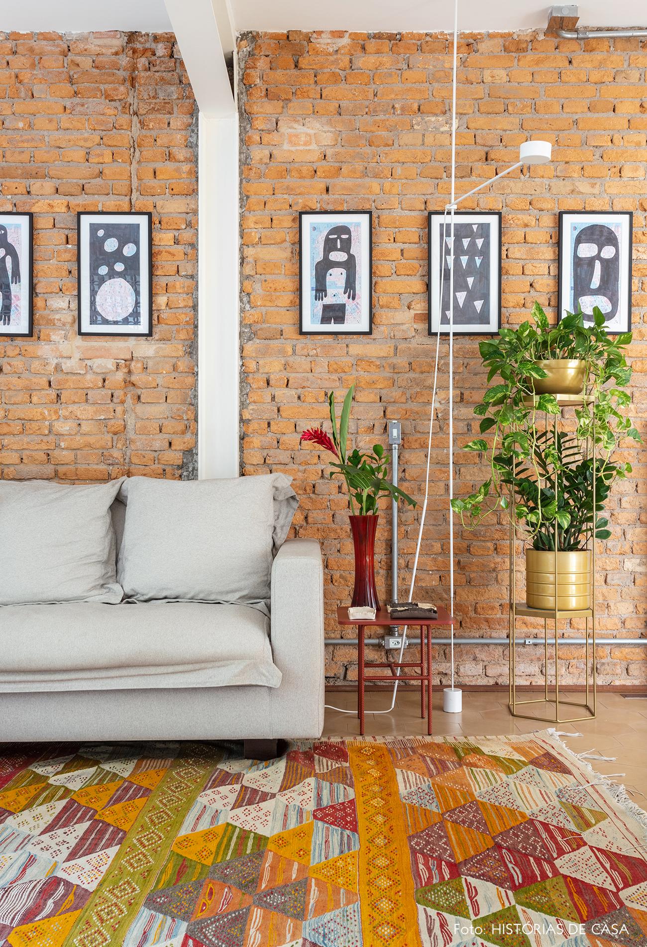 Sala com parede de tijolinhos e tapete colorido, suportes para plantas