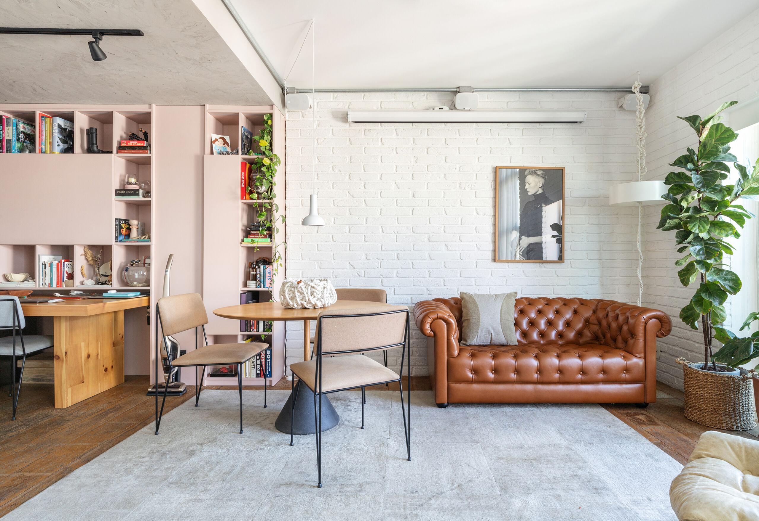 Sala com parede de tijolinho e sofá Chesterfield, apartamento Dre Magalhaes