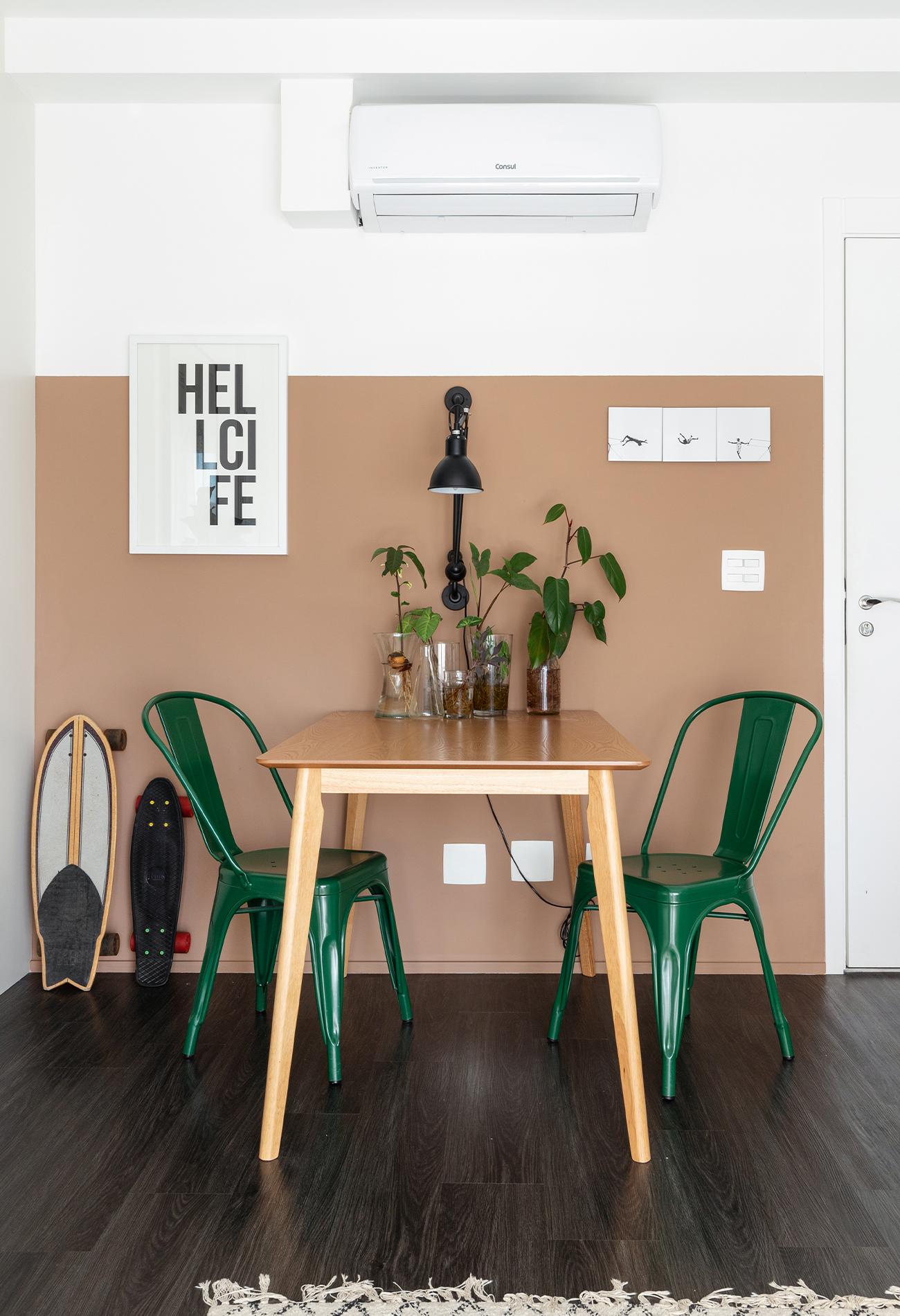 Sala com parede bege rosa com piso de madeira escura e cadeiras verdes e mesa de madeira clara