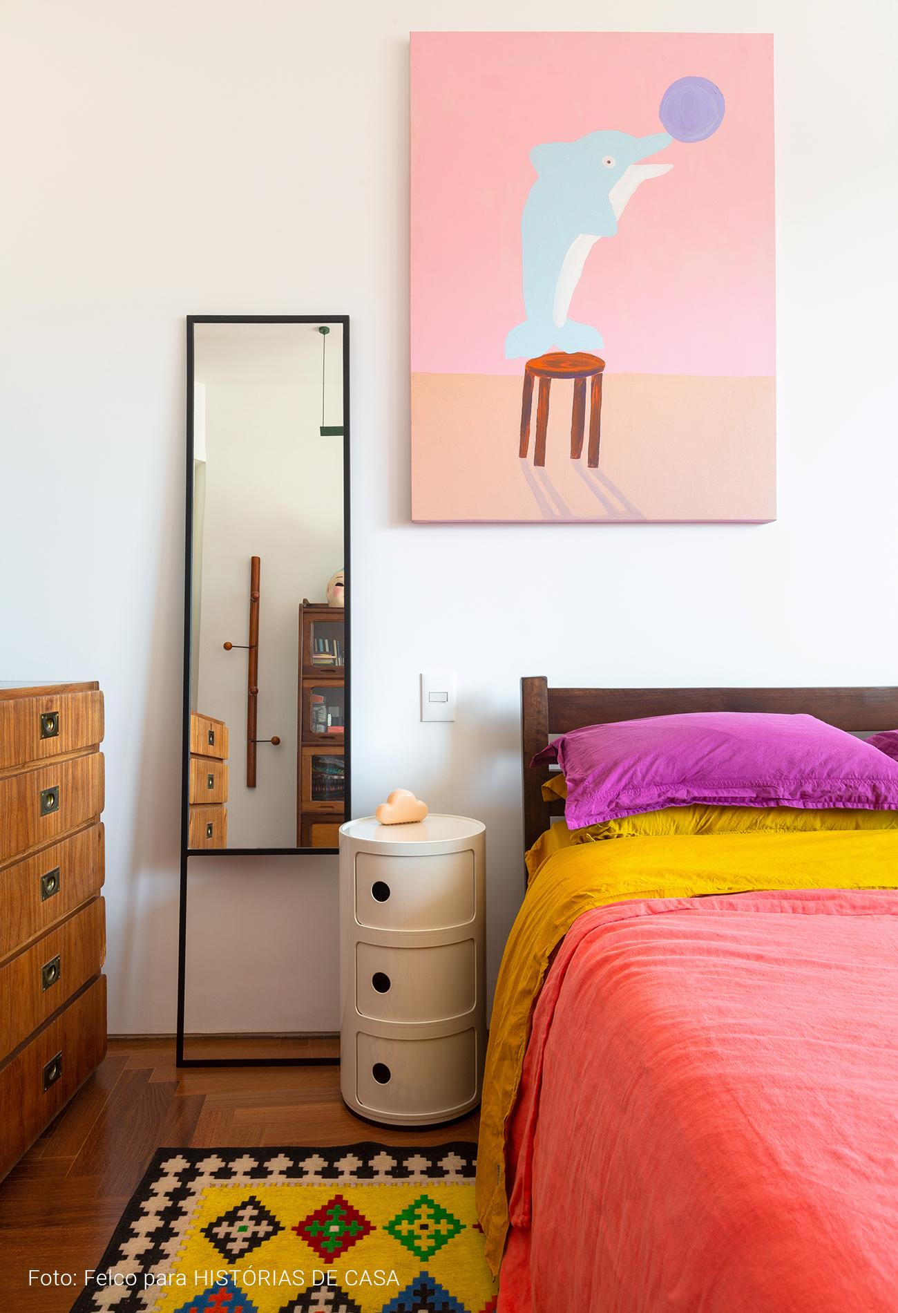 Quarto com roupa de cama colorida e quadro