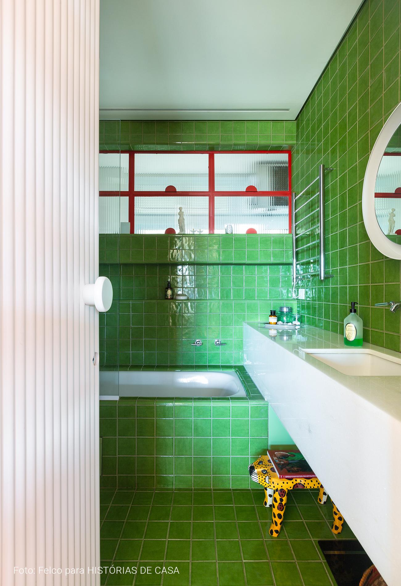 Banheiro com azulejos verdes e serralheria vermelha