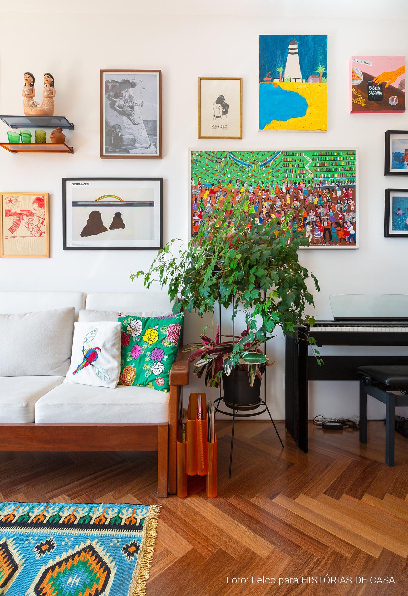 Parede de quadros coloridos sobre o sofá